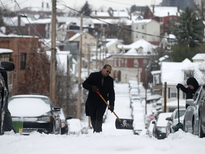 Residents shovel snow on Mt. Washington after a winter storm blanketed the Midwest with snow.(AFP Photo / Jeff Swensen)