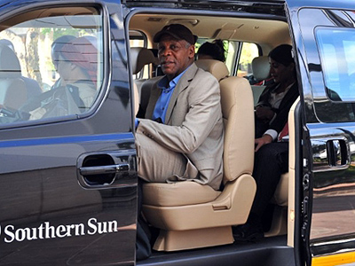 "US actor Danny Glover sits in a car in Johannesburg on March 17, 20111 before accompanying former Haitian President Jean-Bertrand Aristide to Haiti. Glover, who starred in the ""Lethal Weapon"" franchise and ""The Color Purple"", heads a charity involved in Haiti (AFP Photo / Alexander Joe)"
