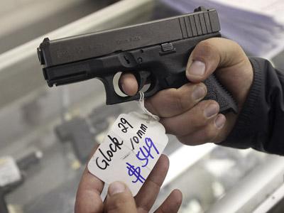 A customer looks over a Glock 29 10mm hand gun at the Guns-R-Us gun shop in Phoenix, Arizona (Reuters/Ralph D. Freso)