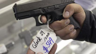 A customer looks over a Glock 29 10mm hand gun at the Guns-R-Us gun shop in Phoenix, Arizona (Reuters/Ralph D. Freso)