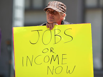 A protestor holds a sign during a demonstration against unemployment benefit cuts on July 11, 2012 in Oakland, California. (Justin Sullivan/Getty Images/AFP)