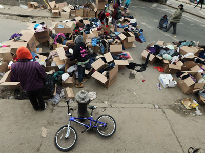 New York : NEW YORK, NY - NOVEMBER 03: People sort through donated clothing on a street corner following Superstorm Sandy at Rockaway Beach ,New York City.(AFP Photo / Mario Tama)