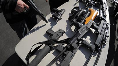 An LAPD officer stands before collected assault weapons during the LAPD Gun Buyback Program event in the Van Nuys area of north Los Angeles, on December 26, 2012. (AFP Photo/Joe Klamar)