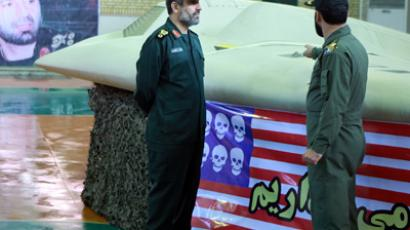 Undated picture shows member of Iran's revolutionary guard pointing at U.S. RQ-170 unmanned spy plane as he speaks with Hajizadeh at unknown location in Iran (	REUTERS/Handout)