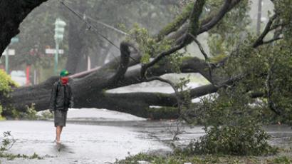 A man stands in front of an uprooted oak tree on Louisiana Avenue as Hurricane Isaac makes land fall in New Orleans (Reuters/Sean Gardner)