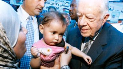 Member of the 'Council of Elders' Delegation former U.S. President Jimmy Carter (R) holds a Palestinian baby girl during a visit to the Elders Delegation in the Arab East Jerusalem neighborhood of Silwan on October 21, 2010 in East Jerusalem
