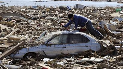 JAPAN, SENDAI: A local resident looks for items from his mother's car amid mud and debris in Sendai, Miyagi Prefecture, on March 14, 2011. (AFP Photo / Toru Yamanaka)