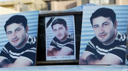 IRAQ, Baghdad : Pictures of Namir Noor-Eldeen, an Iraqi photographer working with Reuters, are seen on top of the vehicle carrying his coffin outside a Baghdad hospital morgue, 13 July 2007. (AFP Photo / Ahmad Al-Rubaye)