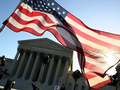 A person carries an American flag while marching in favor of the Patient Protection and Affordable Care Act in front of the U.S. Supreme Court (Mark Wilson/Getty Images/AFP)