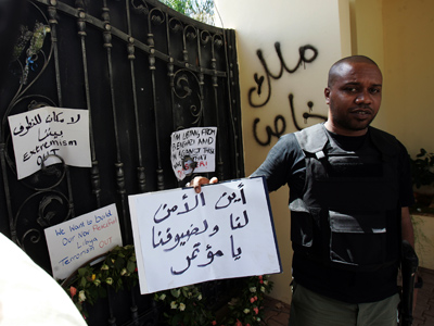 "A Libyan security guard holds a slogan, which reads in Arabic ""Where is the security for us and for our guests"" at the main entrance of the US consulate in Benghazi on September 18, 2012 (AFP Photo / Abdullah Doma)"