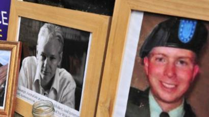 In this dated July 12, 2011 filed photo shows supporters of Wikileaks founder Julian Assange display photographs of Assange (C) and US serviceman Bradley Manning (R) outside the High Court in central London (AFP Photo / Leon Neal / Files)
