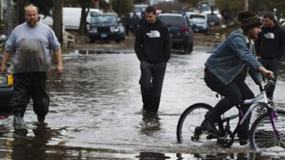 man rides a bike past three others walking through water still sitting in the streets to survey damage from Hurricane Sandy in the New Dorp Beach neighborhood of the Staten Island borough of New York, November 1, 2012.  (Reuters/Lucas Jackson)