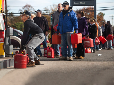 A man fills up jerry cans with gasoline as others wait in line on November 1, 2012 in Hazlet township, New Jersey. (AFP Photo / Andrew Burton)
