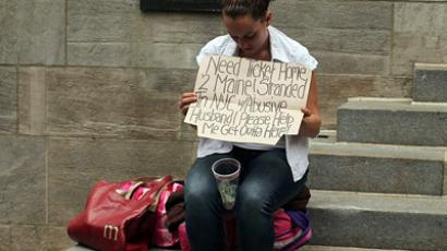 A homeless woman holding a card requesting money in New York City. (AFP Photo/Spencer Platt)