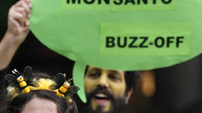An activist from Friends of the Earth Europe wears a bee headband as another holds up a placard during a protest outside the Monsanto's office in Brussels (Reuters/Francois Lenoir)