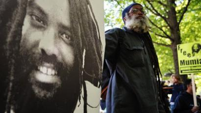 A protestor stands next to an image of Mumia Abu-Jamal during a demonstration outside of the US Department of Justice April 24, 2012 in Washington, DC (AFP Photo / Mandel Ngan)