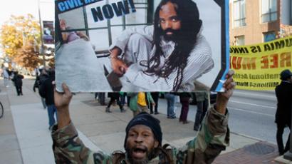 A supporter of black political activist Mumia Abu Jamal holds a sign during a demonstration at the Federal courthouse in Philadelphia, Pennsylvania (Reuters / Tim Shaffer)