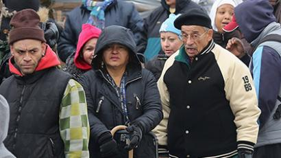 People affected by Superstorm Sandy wait in the cold outside an aid distribution site (John Moore/Getty Images/AFP)