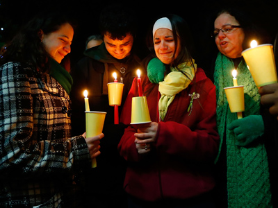 Donna Soto (R), mother of Victoria Soto, the first-grade teacher at Sandy Hook Elementary School who was shot and killed while protecting her students, mourns with her daughter Karly (second from right), daughter Jillian (far left) and son Matthew Soto (second from left), at a candlelight vigil at Stratford High School on December 15, 2012 in Stratford, Connecticut (Jared Wickerham / Getty Images / AFP)