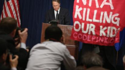 A demonstrator from CodePink holds up a banner as National Rifle Association Executive Vice President Wayne LaPierre delivers remarks during a news conference at the Willard Hotel December 21, 2012 in Washington, DC (Chip Somodevilla / Getty Images / AFP)