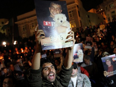 People hold photos of Scott Olsen in Oakland (Justin Sullivan / Getty Images / AFP)