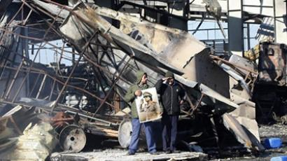 A man holds a portrait of Libyan leader Moamer Kadhafi as he stand in the wreckage of the Boussetta Libyan navy base on March 22, 2011 (AFP Photo / Mahmud Turkia)