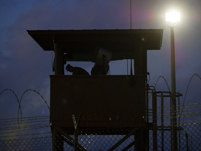 In this photo reviewed by US military officials, a member of the US military mans the guard post before sunrise at Camp Delta, part of the US Detention Center in Guantanamo Bay, Cuba, March 30, 2010. (AFP Photo/Paul J. Richards)