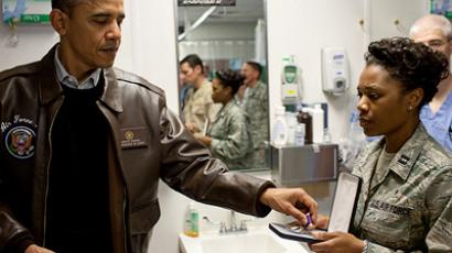 President Barack Obama reaches for a Purple Heart medal which he presented to a wounded soldier at Bagram Air Field in Afghanistan, Dec. 3, 2010. (White House Photo by Pete Souza)