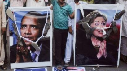 Karachi : Activists of Pakistan Sunni Tehreek (ST) hang shoes on the portraits of US President Barack Obama and US Secretary of State Hillary Clinton. (AFP Photo / Rizwan Tabassum)