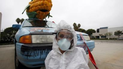 A protester against Genetically Modified Organisms (GMO) is chained to a vehicle while blocking a delivery entrance to a Monsanto seed distribution facility in Oxnard, California September 12, 2012. (Reuters/Mario Anzuoni)