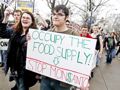 "Members of ""Occupy"" movements in the Midwest protest against Monsanto's agricultural practices in front of the Missouri Botanical Garden during the ""Occupy the Midwest"" regional conference in St. Louis, Missouri March 16, 2012. (Reuters / Sarah Conard)"
