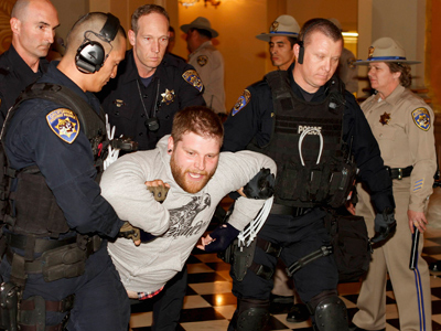 Police carry one of about 40 Occupy the Capitol protesters arrested inside the state Capitol in Sacramento, California (Reuters / Kevin Bartram)