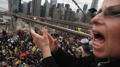 A supporter cheers from the pedstrian overpass as police arrest demonstrators affiliated with the Occupy Wall Street movement after they attempted to cross the Brooklyn Bridge on the motorway on October 1, 2011 New York City (Mario Tama / Getty Images / AFP Photo)