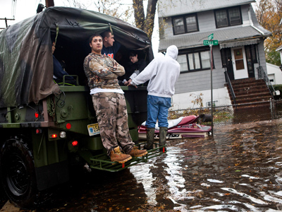 Men patrol a flooded neighborhood after Hurricane Sandy to look for people in need of help on a personally-owned, military-grade personnel carrier, on October 30, 2012, in Little Ferry, New Jersey (Andrew Burton / Getty Images / AFP)