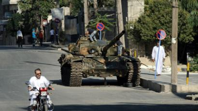 A Syrian man rides a motorcycle past an army tank on which children play, parked along a street of Azaz, in northern Syria on August 19, 2012. (AFP Photo/Phil Moore)