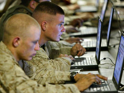 Iraq, Fallujah: US marines from the First Battalion, 5th Marines, Bravo Company, browse the internet at camp Mercury 25 April 2004. (AFP Photo / Nicolas Asfouri)