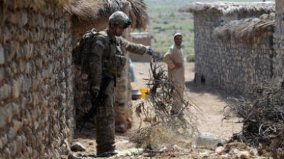 A US soldier from Viper Company 1-26 (Bravo) Infantry searches for arms and ammunitions on an alley while a villager looks on at a village at Combat Outpost (COP) Sabari in Khost province in the east of Afghanistan.(AFP Photo / Ted Aljibe)