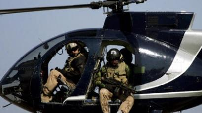 In a file picture dated 05 February 2005, members of the US-based Blackwater private security firm scan Baghdad city centre from their helicopter (AFP Photo / Marwan Naamani)