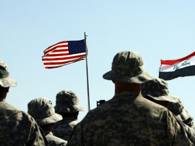 US troops stand to attention in front of American and Iraqi (R) flags during a handover ceremony near the northern Iraqi town of Hawija where the US military formally transferred Contingency Operating Location McHenry to Iraqi security forces on May 15, 2011 (AFP Photo / Ali Al-Saadi)