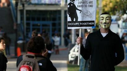 An Occupy protester wears a Guy Fawkes as he holds a sign during a demonstration at the UC Davis campus on November 21, 2011 in Davis, California (AFP Photo / Justin Sullivan)