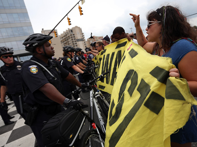 Protesters face off with law enforcement officers and block the road during a march outside the Charlotte Convention Center (AFP Photo / Tom Pennington)