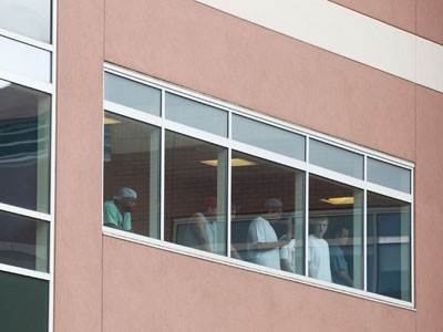Medical staff and visitors look out the window.(AFP Photo / Saul Loeb)