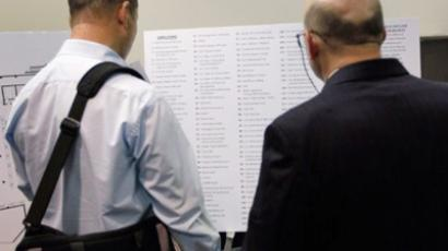 People look at a list of companies attending the job fair (Joe Raedle / Getty Images / AFP)