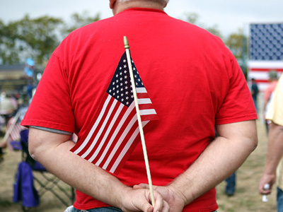 A man holds an American flag during the Tea Party Express tour kick-off on August 27, 2011 in Napa, California. (Justin Sullivan/Getty Images/AFP)