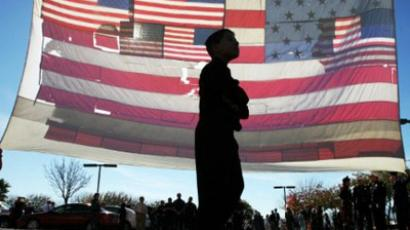 A boy walks past the 9/11 flag, that was recoverd after the terrorist attacks on September 11, 2001 in New York City, outside the entrance of the St. Elizabeth Ann Seton Church, for the funeral of nine-year-old Christina Taylor Green on January 13, 2011 in Tucson, Arizona. (Mamta Popat-Pool/Getty Images/AFP )