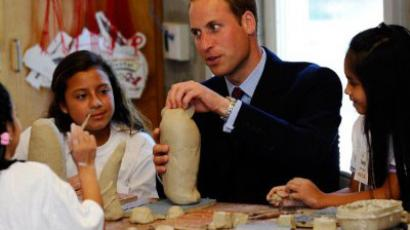 Prince William, Duke of Cambridge, builds separate parts of one giant tortoise with students Blanca Rodriguez (C) and Elliana Rojas (L) and Jesey Aguilar during his visit with Catherine, Duchess of Cambridge at Inner City Arts on July 10, 2011 in Los Angeles, California. (AFP Photo / Pool / Kevork Djansezian)
