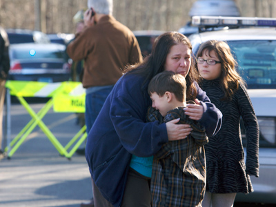 A young boy is comforted outside Sandy Hook Elementary School after a shooting in Newtown, Connecticut, December 14, 2012 (Reuters / Michelle McLoughlin)