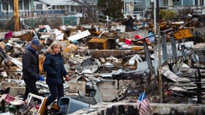 A couple walks amongst the remains of burned houses in the Breezy Point neighborhood of the Borough of Queens on December 25, 2012 in New York City.(AFP Photo / Andrew Burton)