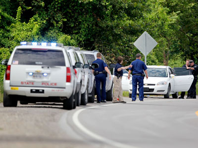 Police insoect a car with bullet holes along LA 3217 after two St. John the Baptist sheriff's deputies were killed and at least one other injured in a shoot out early in the morning.(AFP Photo / Sean Gardner)