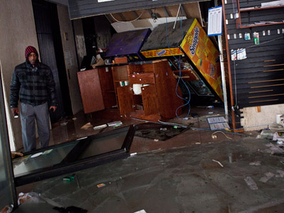 A man surveys the remains of a flooded store following Hurricaine Sandy on October 30, 2012 in the Financial District of New York, United States. (Andrew Burton/Getty Images/AFP)
